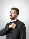 Young groom in tuxedo with bow tie putting plastic comb in his suit pocket. Stock Image