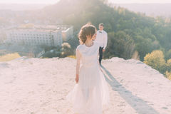 Young groom in white shirt and bow standing behind the dancing beautiful bride wearing bridal dress Royalty Free Stock Image