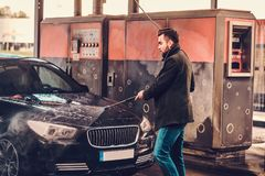 Young groomed man is washing his own car at car washing station royalty free stock image