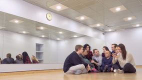 Young group of actors discussing a future performance in the theatre. Young group of actors sits on floor and discussing the future performance. One of the girl stock footage