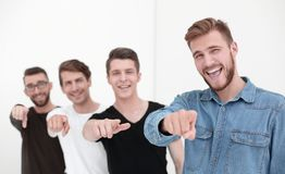 Young group of cheerful students pointing at you. royalty free stock photography