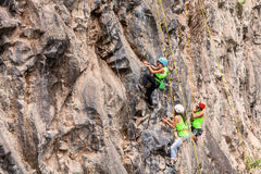 Young Group Of Climbers Climbing A Rock Wall Royalty Free Stock Photos