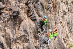 Young Group Of Climbers Climbing A Rock Wall Royalty Free Stock Photos