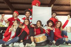 Young group of fans dressed in red color watching a sports event. In the stands of a stadium stock image
