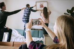 Young group of friends decorating the apartment and a woman taking a photo. Young group of friends decorating the apartment and a women taking a photo stock photo