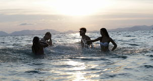 Young Group Of Friends Splashing In Sea At Sunset, Cheerful People Having Fun In Water On Beach During Summer Vacation. Slow Motion 60 stock video footage