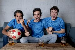 Young group of happy and excited men watching a football game on the couch. Happy young group of football fans caucasian men watching the football and Stock Photos