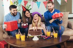 Happy friends celebrating birthday at home and having fun stock image