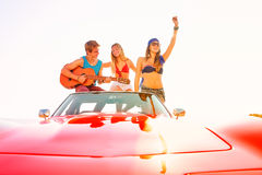 Young group having fun on beach playing guitar Stock Photography