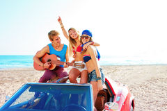 Young group having fun on beach playing guitar Royalty Free Stock Photo