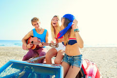 Young group having fun on beach playing guitar Stock Images