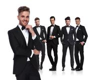 Young group leader in tuxedo stands in front and smiles royalty free stock image