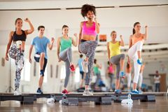 Group of people exercising on stepper Stock Photos