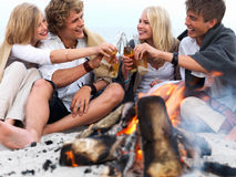 Young group of people sitting by bonfire at the be Royalty Free Stock Photo