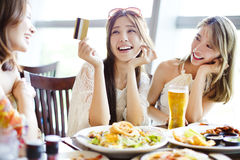 Young group showing credit card and chatting in restaurant Royalty Free Stock Photos