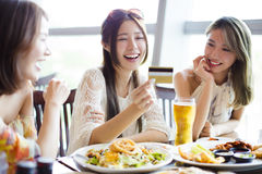 Young group showing credit card and chatting in restaurant Stock Photography