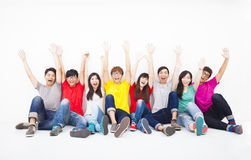 Young group sitting together against white wall Stock Photography