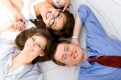 The young group of smiling business people. Lying on floor Royalty Free Stock Photography