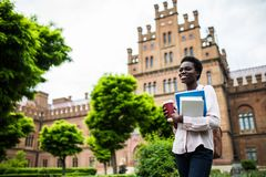 Young group of students with backpacks and books with Campus as a background. Afro American girl with notebooks and cup of coffee stock images
