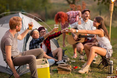 Young group toasting with bottles and glasses of beer in campgro Royalty Free Stock Photo