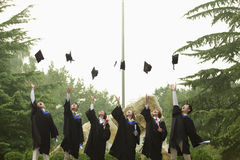 Young Group of University Graduates Throwing Mortarboards in the Air Stock Photo