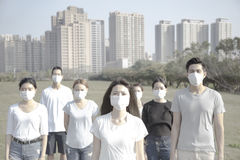 Young group wearing mouth mask against air pollution in city Royalty Free Stock Images
