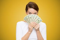 Grumpy woman covering face with heap of bills looking at camera on yellow background royalty free stock image