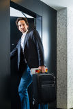 Young guest with luggage entering hotel room Royalty Free Stock Photo