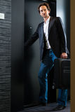 Young guest with luggage entering hotel room Stock Photography
