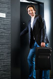 Young guest with luggage entering hotel room Stock Photos