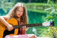 Young guitar student playing at lake. Stock Images
