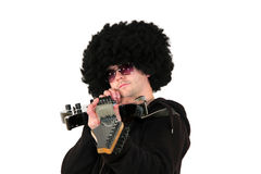 Young guitarist aiming with his guitar. A young guitarist with a wig and sunglasses aiming with his guitar towards camera, isolated on white background Stock Photos