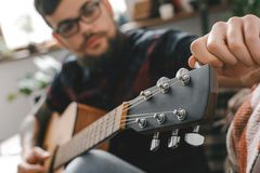 Young guitarist hipster at home with guitar fixing tuning pegs close-up. Young male guitarist hipster indoors holding guitar fixing tuning pegs close-up blurred Stock Images