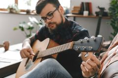 Young guitarist hipster at home with guitar fixing tuning pegs. Young male guitarist hipster indoors holding guitar fixing tuning pegs Stock Photo