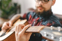 Young guitarist hipster at home with guitar holding strings close-up. Young male guitarist hipster indoors with guitar sitting holding strings close-up blurred royalty free stock photos