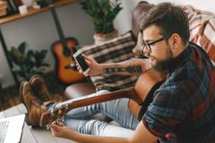 Young guitarist hipster at home with guitar tuning using app. Young male guitarist hipster indoors tuning guitar using smartphone application concentrated Stock Images