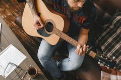 Young guitarist hipster at home playing guitar top view close-up. Young male guitarist hipster indoors playing guitar top view close-up inspired royalty free stock photo