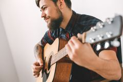 Young guitarist hipster at home playing guitar using mediator close-up. Young male guitarist hipster indoors playing guitar using mediator smiling close-up Stock Image