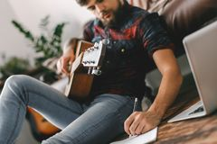 Young guitarist hipster at home sitting on the floor with guitar writing melody. Young male guitarist hipster indoors with guitar sitting on the floor writing Royalty Free Stock Images