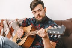 Young guitarist hipster at home sitting playing guitar serious. Young male guitarist hipster indoors sitting playing guitar serious close-up stock photo