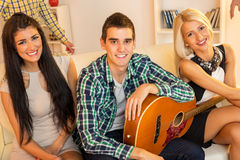 Young Guitarist With Hot Girls. Young guy with an acoustic guitar at house party, sit on the couch between two pretty girls. With a smile looking at the camera Stock Photos