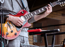Young guitarist performing on outdoor stage during live concert. Young guitarist performing during live concert on outdoor stage Royalty Free Stock Image