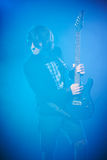 Young guitarist performing on stage. Smoky scenic Stock Images