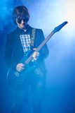 Young guitarist performing on stage. Smoky scenic Stock Photo