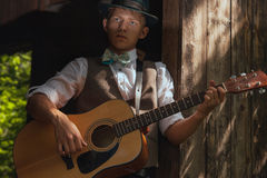 Young guitarist plays acoustic guitar on countryside Royalty Free Stock Images