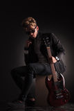 Young guitarist sitting and holding his jacket by it's collar. Looking at the camera with his electric guitar near him, on dark studio background Royalty Free Stock Images