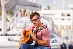 Young guitarist sitting on pier. Romance music sound talent masculinity concept. Young guitarist sitting on pier. Man playing on guitar in front of boat royalty free stock photos