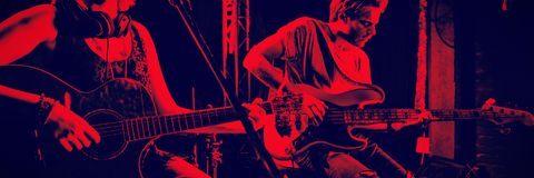 Guitarists performing at nightclub. Young guitarists performing on stage at nightclub Royalty Free Stock Images