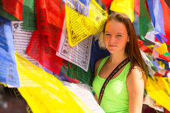 Young gute girl and Buddhist prayer flags flying in the Buddhist monastery. Stock Photo