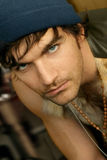 Young Guy. Portrait of a young alternative type male model in cap in beaded necklace Royalty Free Stock Image